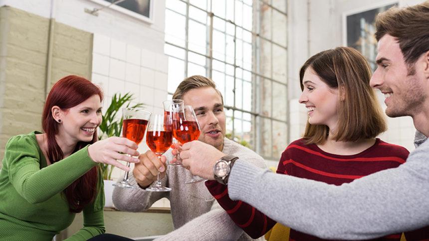 Freunde trinken Wein auf Sofa
